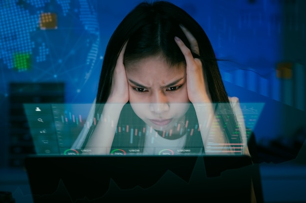 Young asian businesswoman has a headache. trader looking computer have financial issues with graphs in office at night.