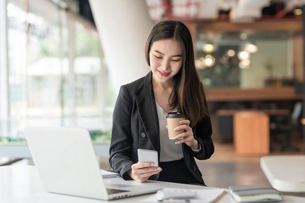 Молодой азиатский бизнесмен, держащий кофе и использующий смартфон, ноутбук в офисе. Premium Фотографии