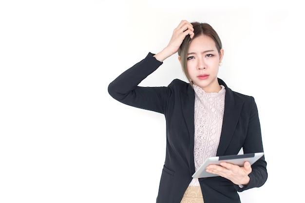 흰색 바탕에 혼란스러운 감정으로 디지털 태블릿을 들고 있는 젊은 아시아 여성