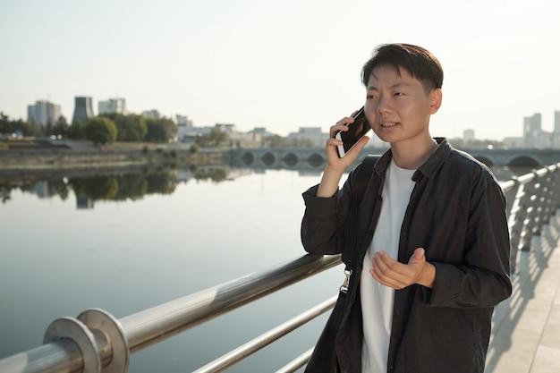 스마트 캐주얼웨어를 입은 젊은 아시아 여성 사업가가 휴대전화로 통화