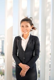 Молодая азиатская коммерсантка в костюме stading снаружи.