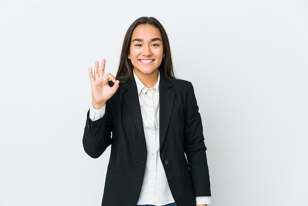 白い壁に孤立した若いアジアの実業家は、陽気で自信を持って大丈夫なジェスチャーを示しています。