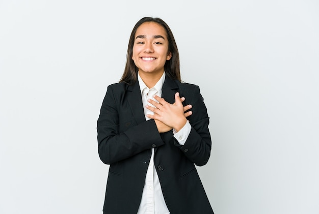 Young asian businesswoman isolated on white wall has friendly expression, pressing palm to chest. love concept.
