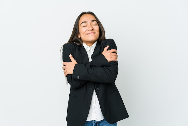Young asian businesswoman isolated on white wall hugs, smiling carefree and happy.