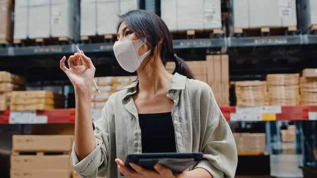 Молодой азиатский менеджер бизнес-леди, носящий склад маски для лица, используя цифровой планшет, проверяя инвентарь
