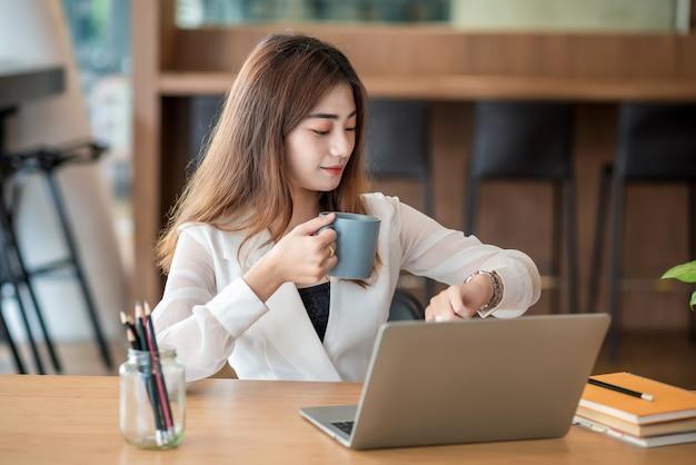 Молодой азиатский бизнесмен на перерыв на кофе и используя портативный компьютер в офисе