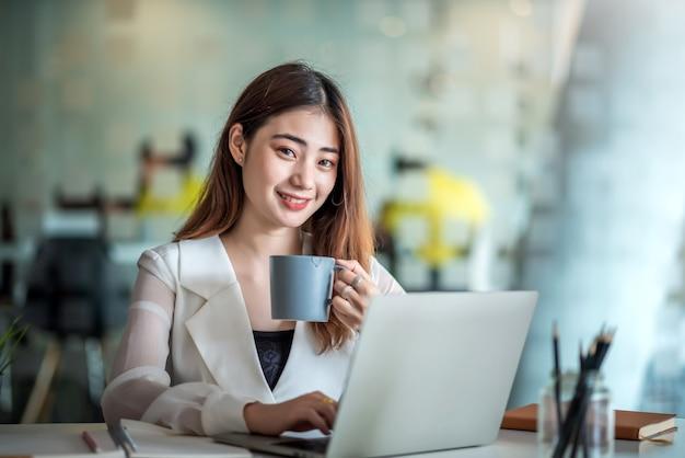 Молодая азиатская коммерсантка на перерыв на кофе и используя портативный компьютер в офисе.