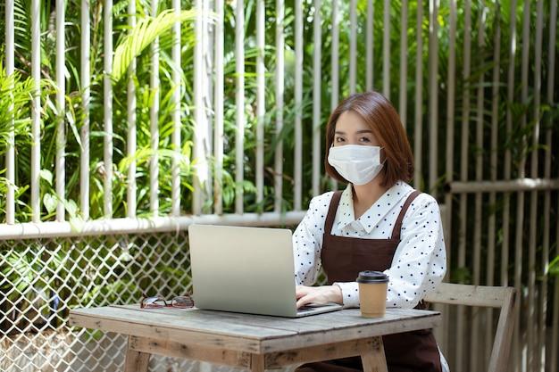 젊은 아시아 사업가는 covid-19를 보호하기 위해 커피 숍 마스크를 소유하고 모든 장치에 대한 지불로 고객으로부터 온라인 주문을받습니다.