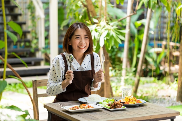 Young asian businesswoman owns a coffee shop and recommend the food menu available in the store
