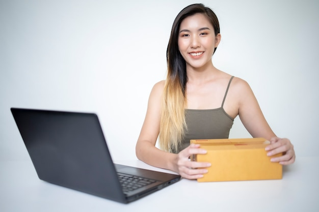 A young asian businesswoman packing products in a package according to the order the customer has ordered