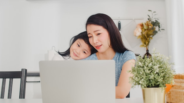 젊은 아시아 사업가 심각한, 스트레스, 피곤하고 아픈 집에서 랩톱에서 작업하는 동안. 아침에 집에서 현대 부엌에서 열심히 일하고 그녀의 어머니를 위로하는 어린 딸.
