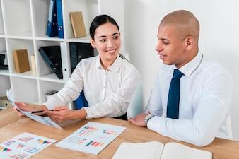 彼女の同僚にビジネスレポートを示す若いアジア女性実業家