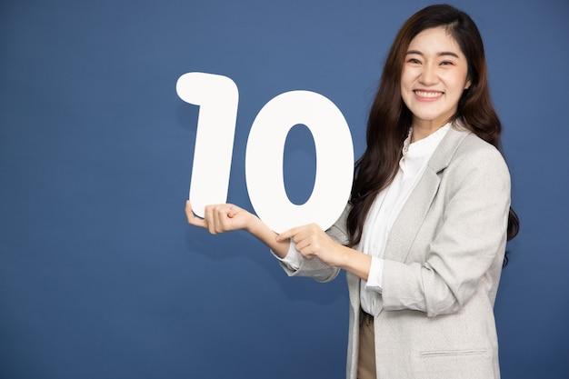 파란색 배경에 고립 된 번호 10 또는 10을 보여주는 젊은 아시아 사업가