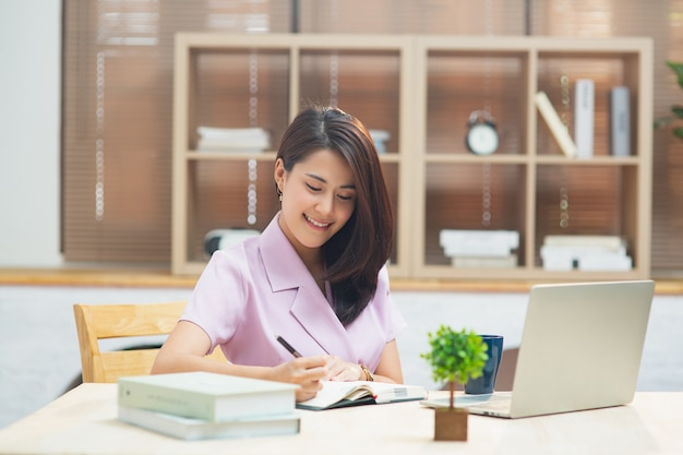 거실에 앉아 노트북으로 집에서 일하는 젊은 아시아 여성