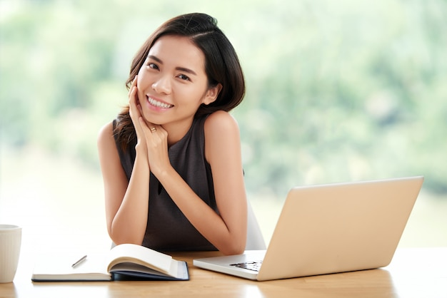Young asian businesswoman sitting at table with notebook and laptop on it