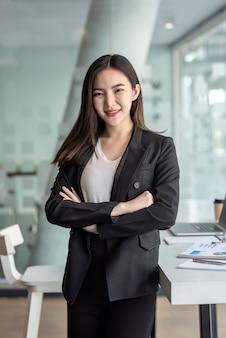 オフィスに立っている若いアジアの実業家。