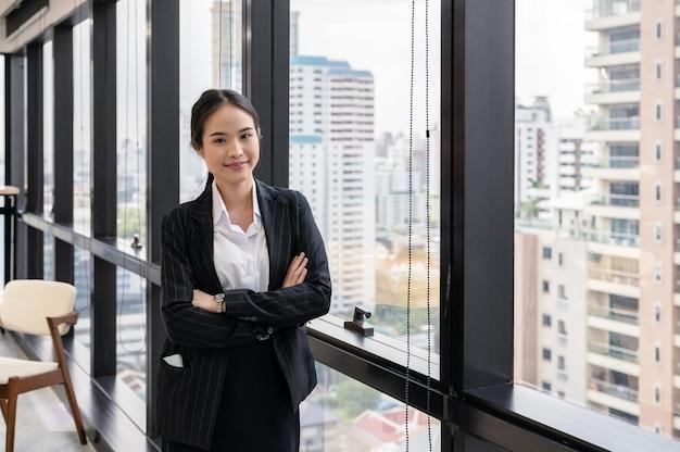 立っている若いアジア女性実業家のオフィスで交差した腕