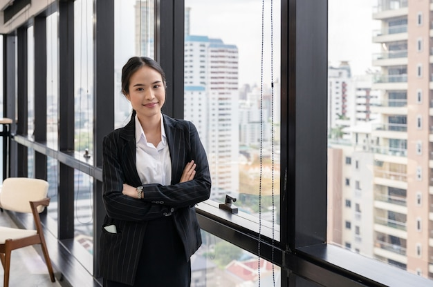 Young asian businesswoman standing crossed arm in the office