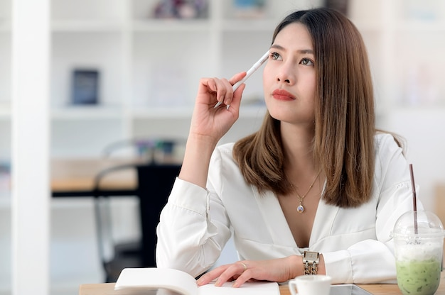 Молодая азиатская коммерсантка думая о работе на co-месте для работы.