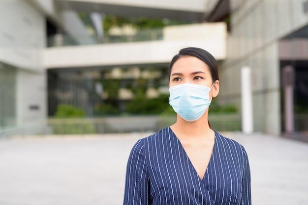 Молодая азиатская бизнес-леди думает с маской для защиты от вспышки вируса короны в городе