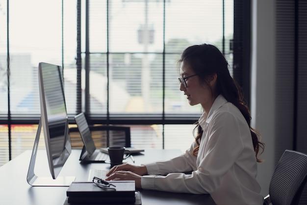 Молодой азиатский бизнесмен, набрав клавиатуру на портативном компьютере в офисе