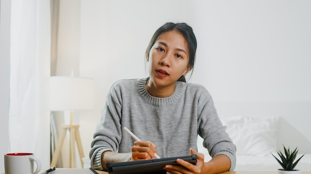 Young asian businesswoman using computer laptop talk to colleagues about plan in video call meeting while working from home at bedroom