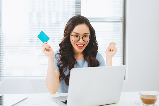 Молодая азиатская бизнес-леди, использующая кредитную карту для онлайн-оплаты