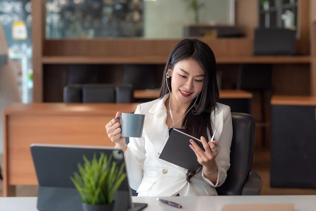 Молодой азиатский бизнесмен в наушниках, держащий кофейную чашку, сидит расслабиться в офисе.