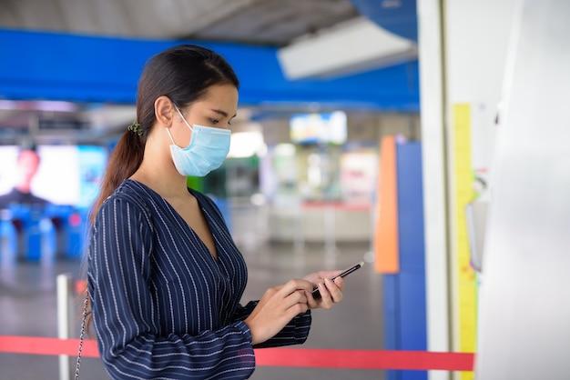 Молодая азиатская бизнес-леди с маской покупает билет по телефону на станции надземного метро