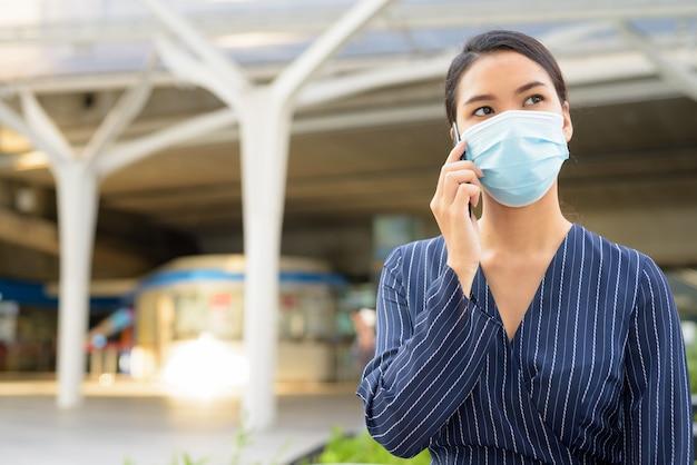 Молодая азиатская бизнес-леди с маской для защиты от вспышки вируса короны разговаривает по телефону в городе