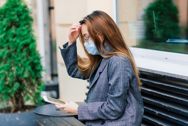 Молодой азиатский бизнесмен с маской, используя телефон и сидя на расстоянии за пределами кафе