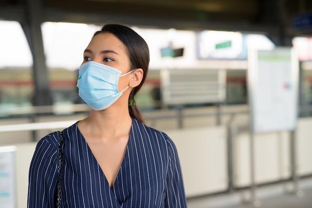 スカイトレインの駅で待っているマスクを持つ若いアジアの実業家