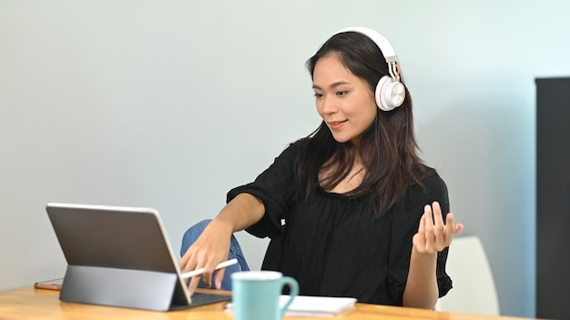 Молодой азиатский бизнесмен работает дома и виртуальная видеоконференция, встречающаяся с коллегами по бизнесу.