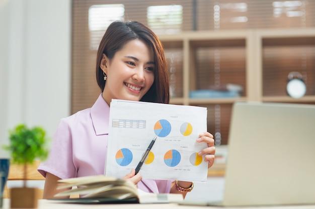화상 회의 중 노트북에 비즈니스 보고서를 보여주는 집에서 일하는 젊은 아시아 여성