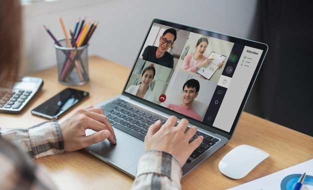 Young asian businesswoman working remotely from home and virtual video conference meeting with colleagues business people. social distancing at home office concept.