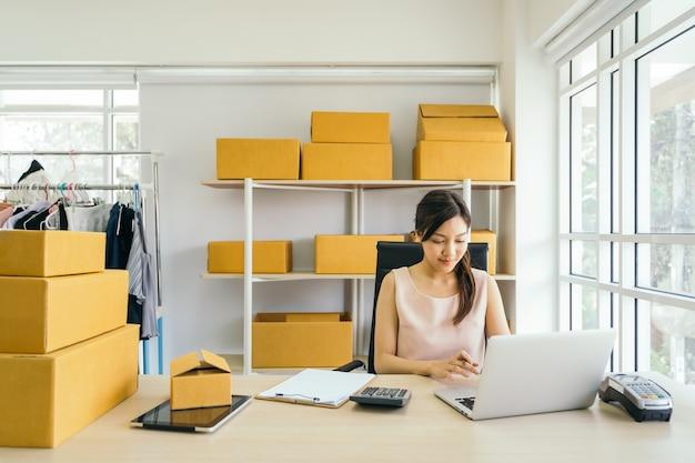 Молодая азиатская коммерсантка работая с компьтер-книжкой в офисе