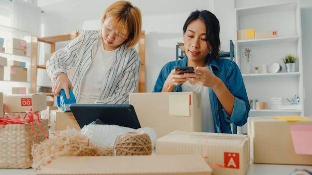 Giovani donne di affari asiatiche che utilizzano il telefono cellulare che riceve l'ordine di acquisto e che controlla il prodotto sul lavoro di riserva all'ufficio domestico