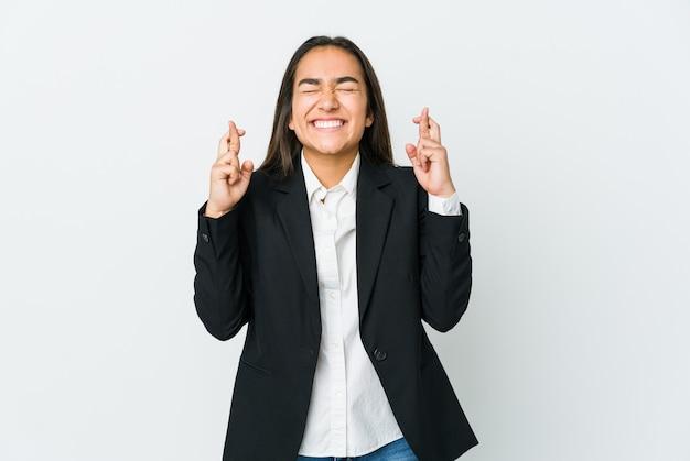 運を持っているために指を交差させる白い背景で隔離の若いアジアのbussines女性