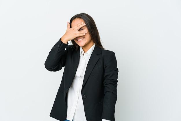 흰 벽에 고립 된 젊은 아시아 탈취 여자는 얼굴을 덮고 당황, 손가락을 통해 전면에 깜박