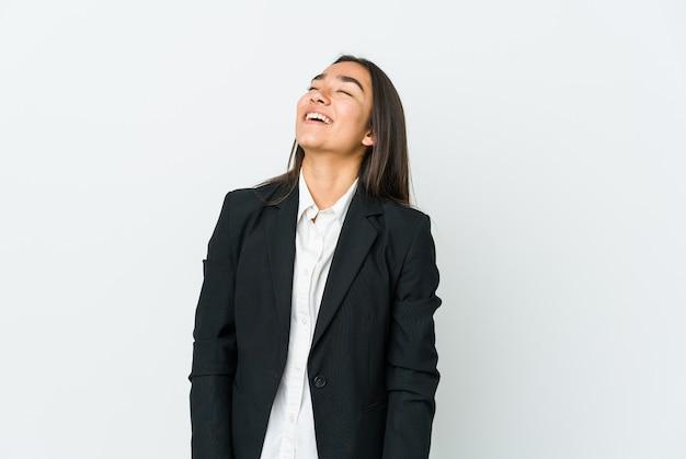 흰 벽에 고립 된 젊은 아시아 탈취 여자 편안하고 행복한 웃음, 목 뻗어 보여주는 이빨