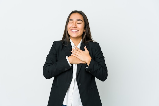 Young asian bussines woman isolated on white wall laughing keeping hands on heart, concept of happiness.