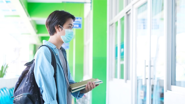 Young asian campus student man wearing protection mask while walking in campus