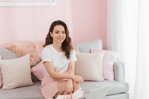 中小企業のオンラインで働く若いアジアのカジュアルな女性がホームオフィスに座って笑っています。フリーランスのスタートアップ中小企業の所有者、オンライン販売、eコマース。