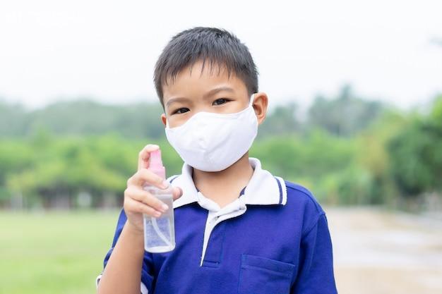 Маска ткани молодого азиатского мальчика ребенка нося и держать бутылку брызга спирта в его руке для предотвращения болезни coronavirus или covid-19.