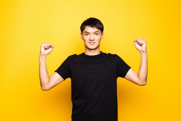 Il giovane uomo cinese asiatico che celebra sorpreso e stupito per successo con le armi alzate e apre gli occhi che controllano la parete gialla isolata. concetto di vincitore.