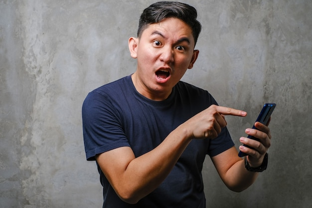 Young asian chinese man shouting and looking to camera while pointing at his smartphone receiving bad news, over concrete wall background