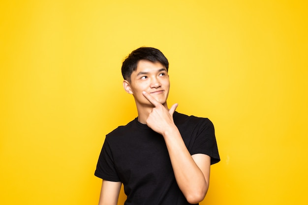 Young asian chinese man with hand on chin thinking about question, pensive expression standing over isolated yellow wall . smiling with thoughtful face. doubt concept.