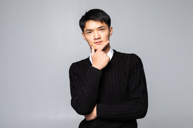 Young asian chinese man with hands on chin standing over isolated white wall