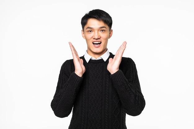 격리 된 흰 벽 위에 서있는 젊은 아시아 중국 놀된 사람