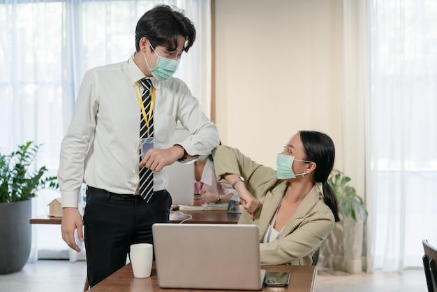 コロナウイルスcovid-19の流行中にオフィスでぶつかる肘でマスクの挨拶を身に着けている若いアジアの同僚の男性と女性